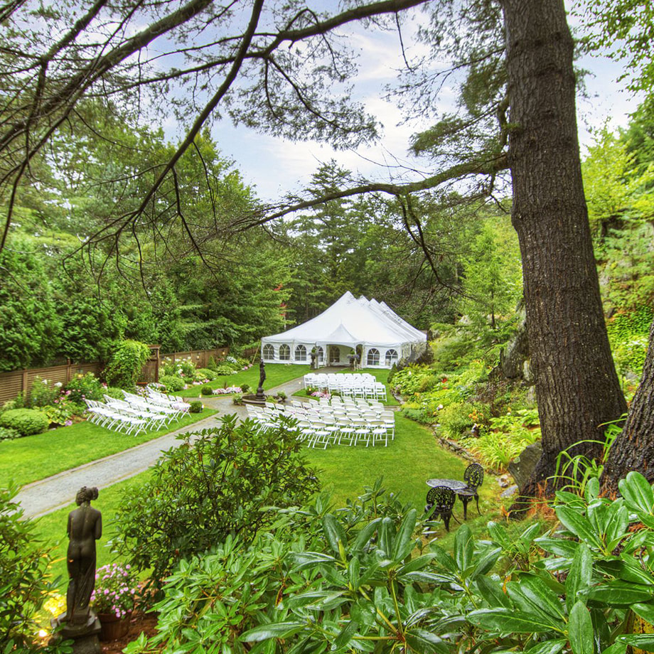 A lush garden surrounding a white tent, rows of chairs, and a fountain